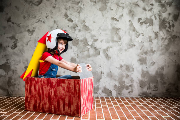 Child driving in a car made of cardboard box stock photo