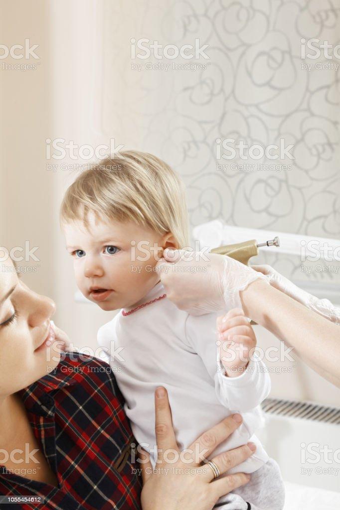 Child ear piercing stock photo