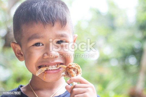 child eating a fries chicken leg.