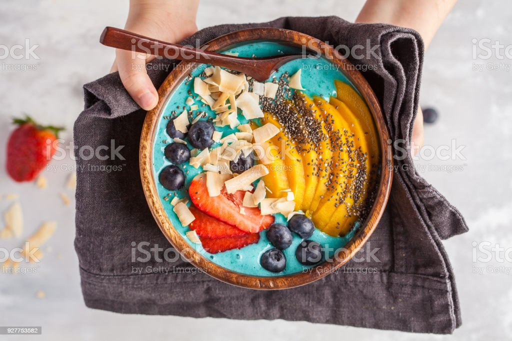 Child eating blueberry smoothie bowl with mango and coconut, top view, copy space. Vegan Healthy Food Concept. stock photo