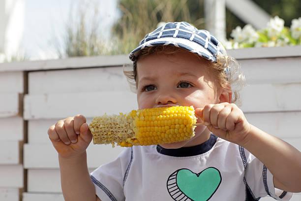 Niño comiendo hervida maíz - foto de stock