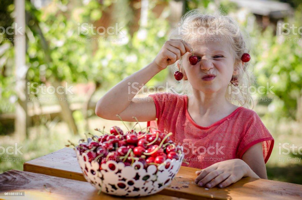 child eating cherry fruit stock photo