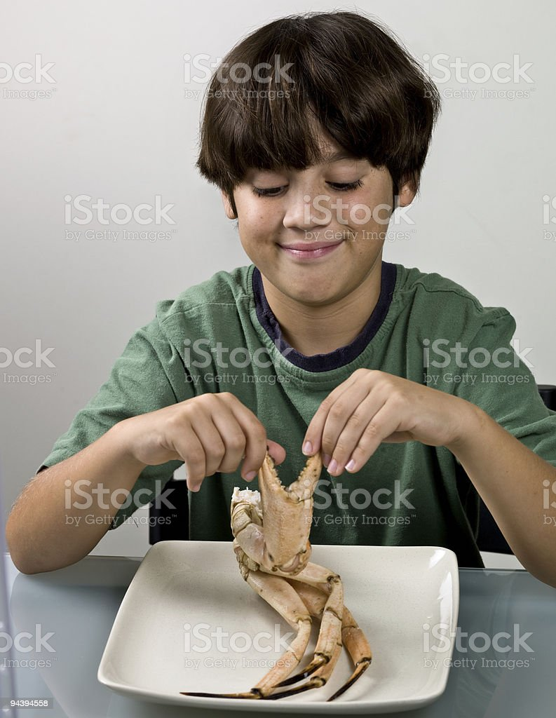 Child eating crab legs stock photo