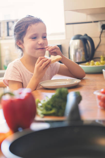 Child eating in the kitchen. She is eating a sandwich. stock photo
