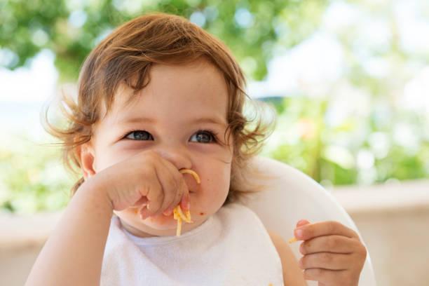 kinder essen nudeln - kinderstuhl und tisch stock-fotos und bilder
