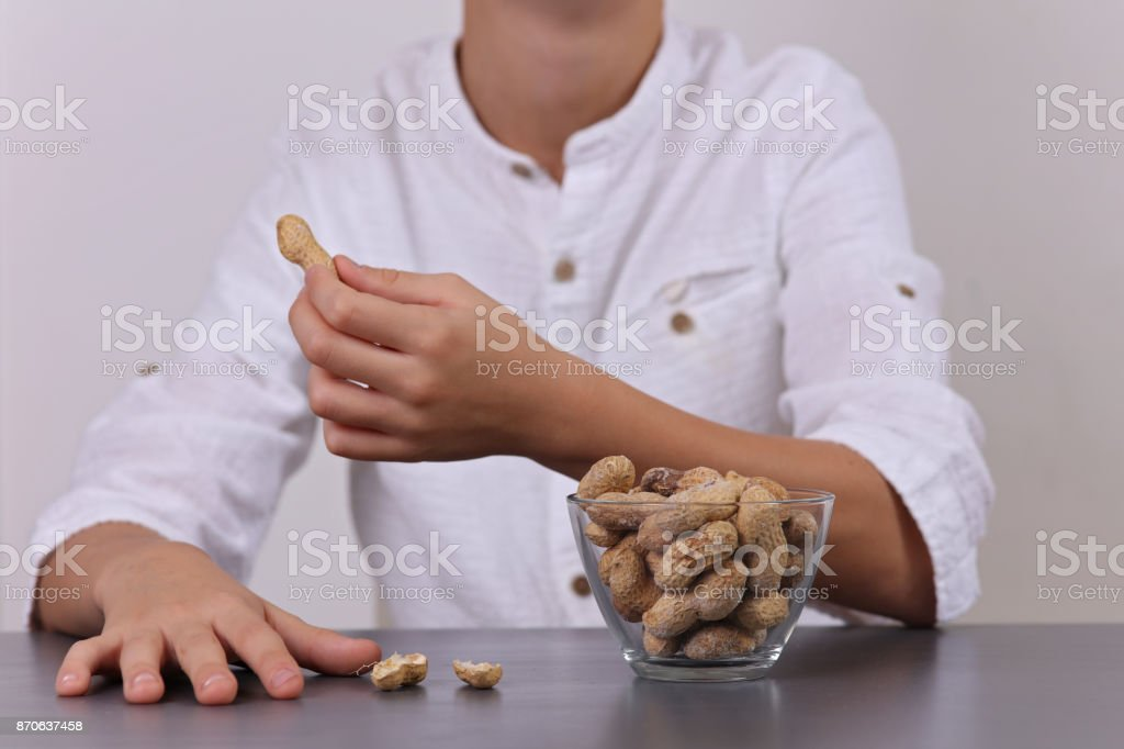 Child eating peanuts. Food allergy concept stock photo