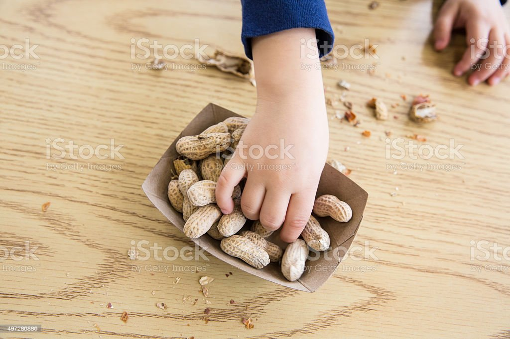 Child eating Peanuts stock photo