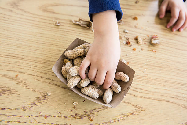 child eating peanuts - pinda voedsel stockfoto's en -beelden