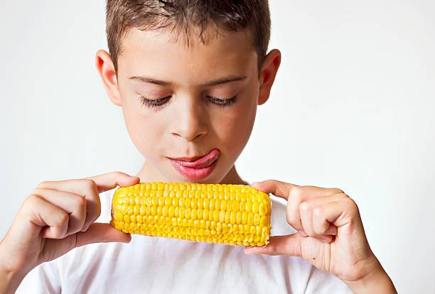 Child eating sweet corn stock photo