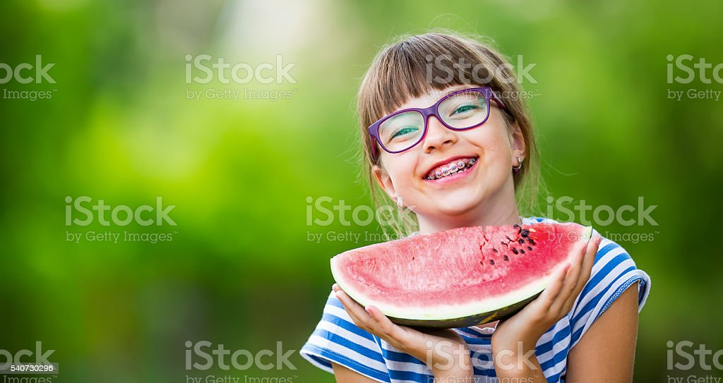 Child eating watermelon. Kids eat fruits in the garden. Child eating watermelon. Kids eat fruits in the garden. Pre teen girl in the garden holding a slice of water melon. happy girl kid eating watermelon. Girl kid with gasses and teeth braces.Child eating watermelon. Kids eat fruits in the garden. Pre teen girl in the garden holding a slice of water melon. happy girl kid eating watermelon. Girl kid with gasses and teeth braces. Cheerful Stock Photo