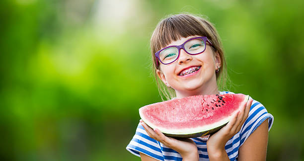 Child eating watermelon. Kids eat fruits in the garden. stock photo