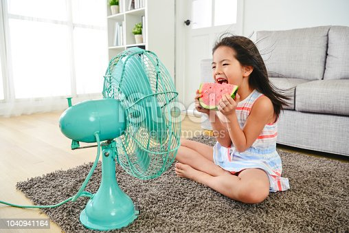 child eating watermelon with two hands. sitting in front of the electric fan.  taking a big bite delightfully.