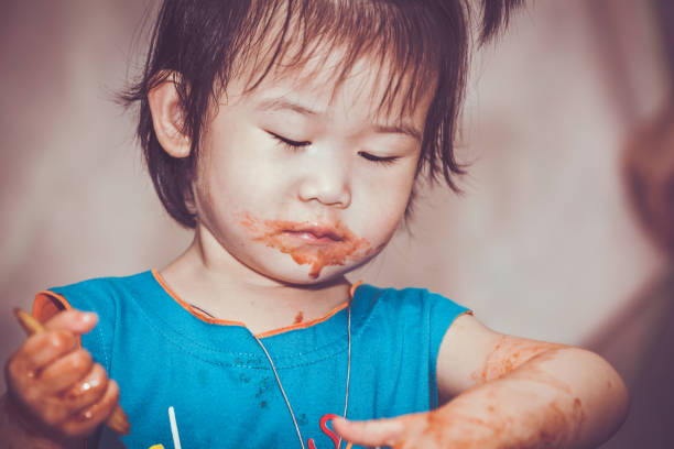 Child eating with a stained face. Do it yourself concept. Vintage tone. stock photo