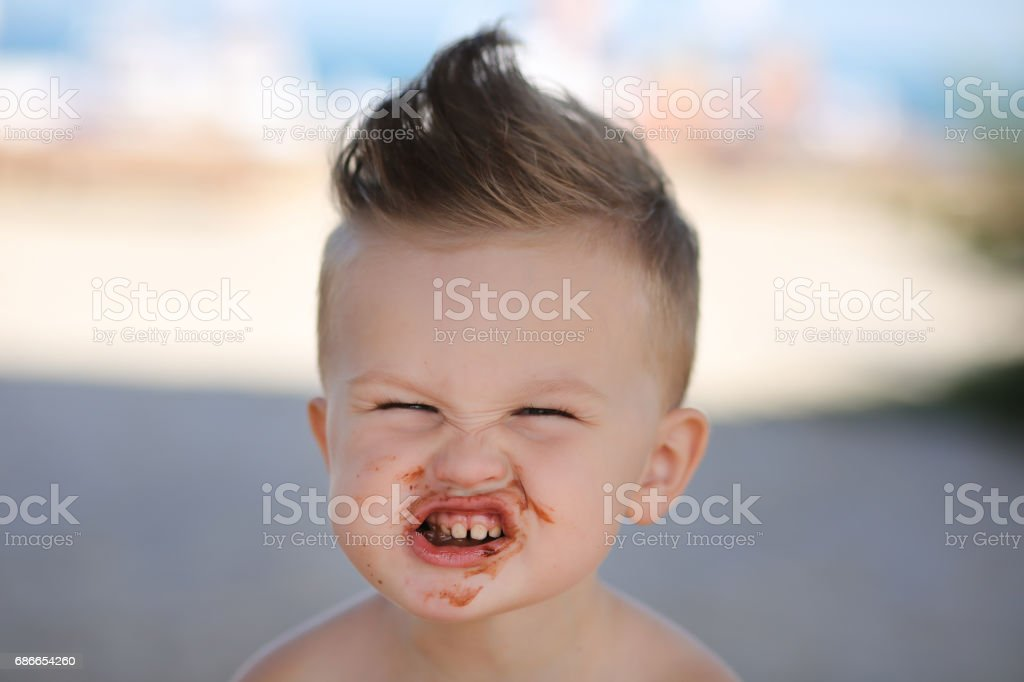 Child eats chokolate with full stength on a beach royalty-free stock photo
