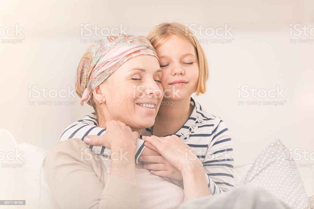 Child embracing ill mother stock photo