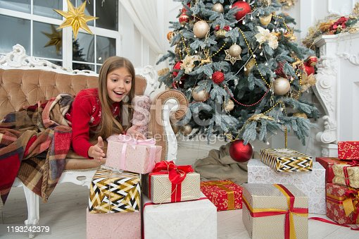 Child enjoy the holiday. Happy new year. Winter. Cxmas online shopping. Family holiday. Christmas tree and presents. The morning before Xmas. Little girl.