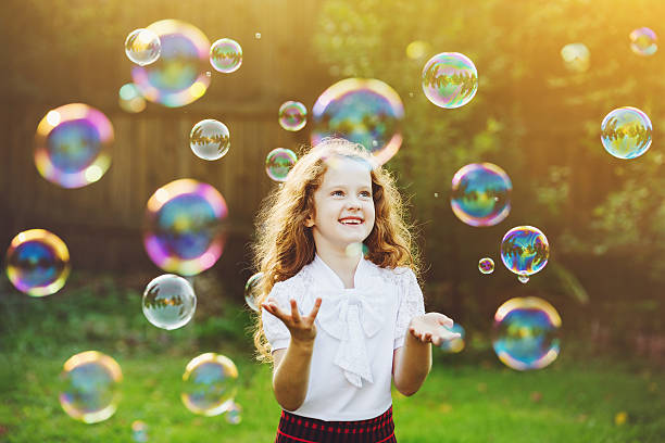 Child enjoying blowing soap bubbles in the summer park – Foto