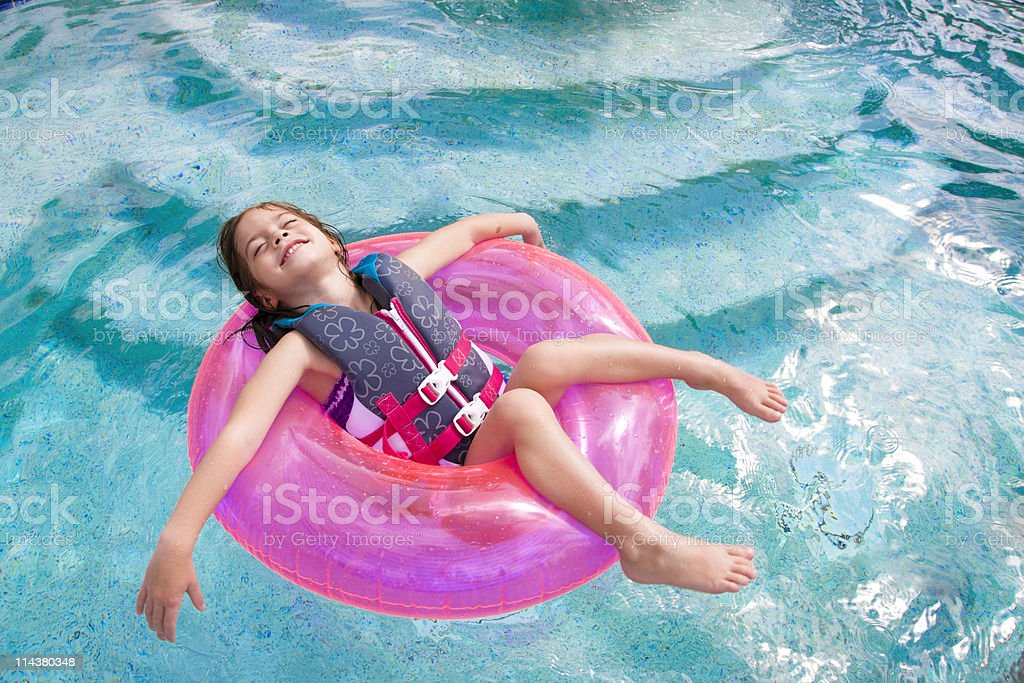 Child enjoying playing in the swimming pool stock photo