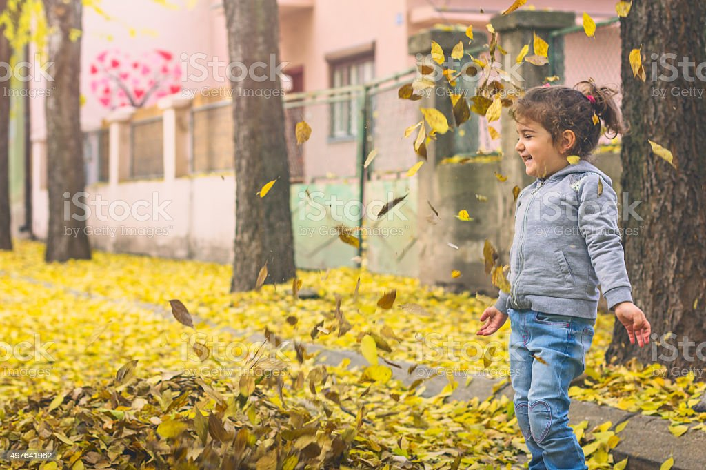 child enjoys playing with leaves stock photo