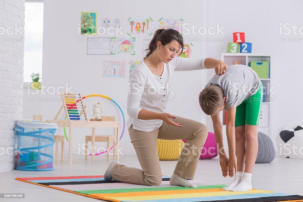 Child exercising with physiotherapist stock photo