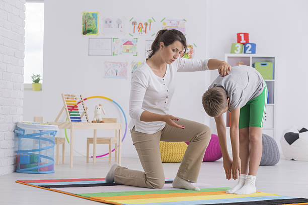 child exercising with physiotherapist - skoliose stock-fotos und bilder