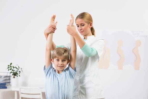 Child exercising with physiotherapist stock photo