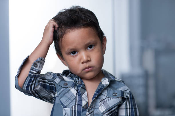 A child exibiting a mood disorder or depressed irritability, expressing sadness and pulling of his hair. stock photo
