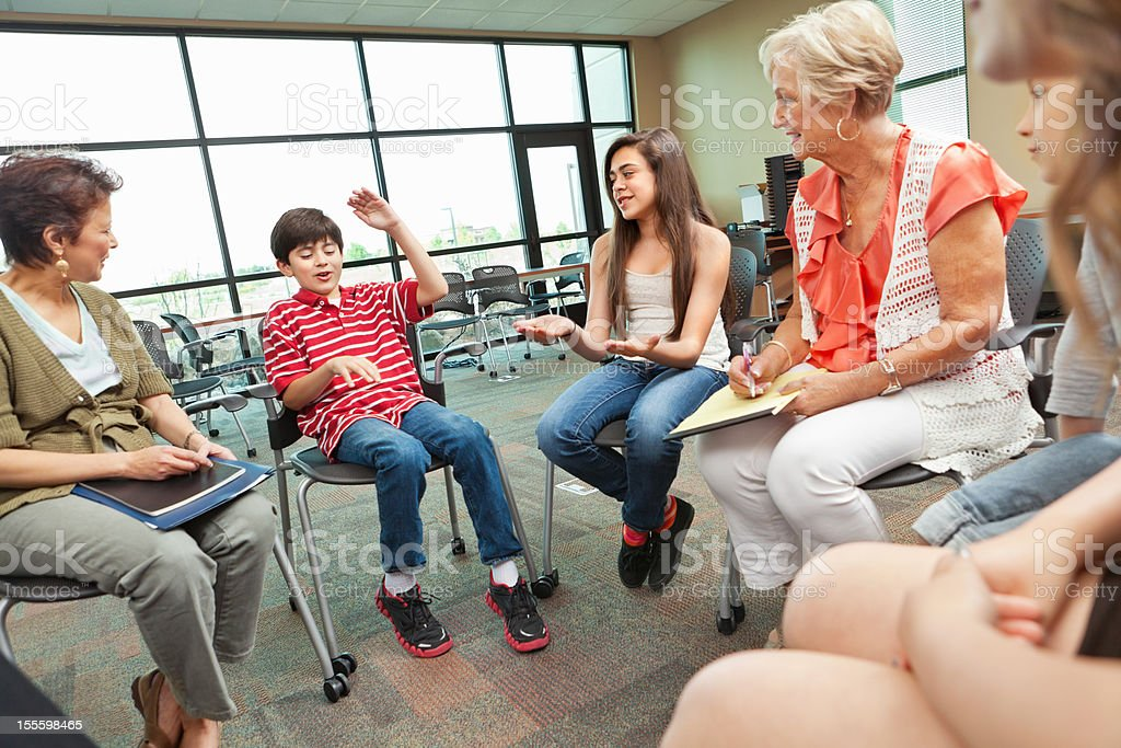 Child explaining something to group of adults and children stock photo