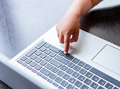 istock Child explores silver metal laptop. Curious toddler boy presses buttons. 1217168478