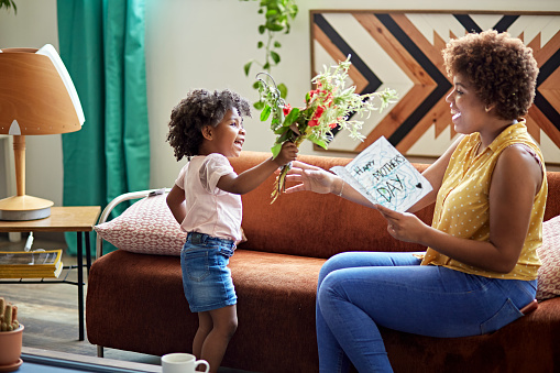 Side view of 3 year old Afro-Caribbean girl giving mother in mid 20s bouquet of flowers and homemade card.