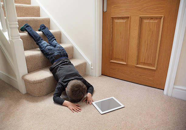 Child falling down the stairs Child falling down the stairs whilst playing on digital tablet not concentrating concept for safety at home careless stock pictures, royalty-free photos & images