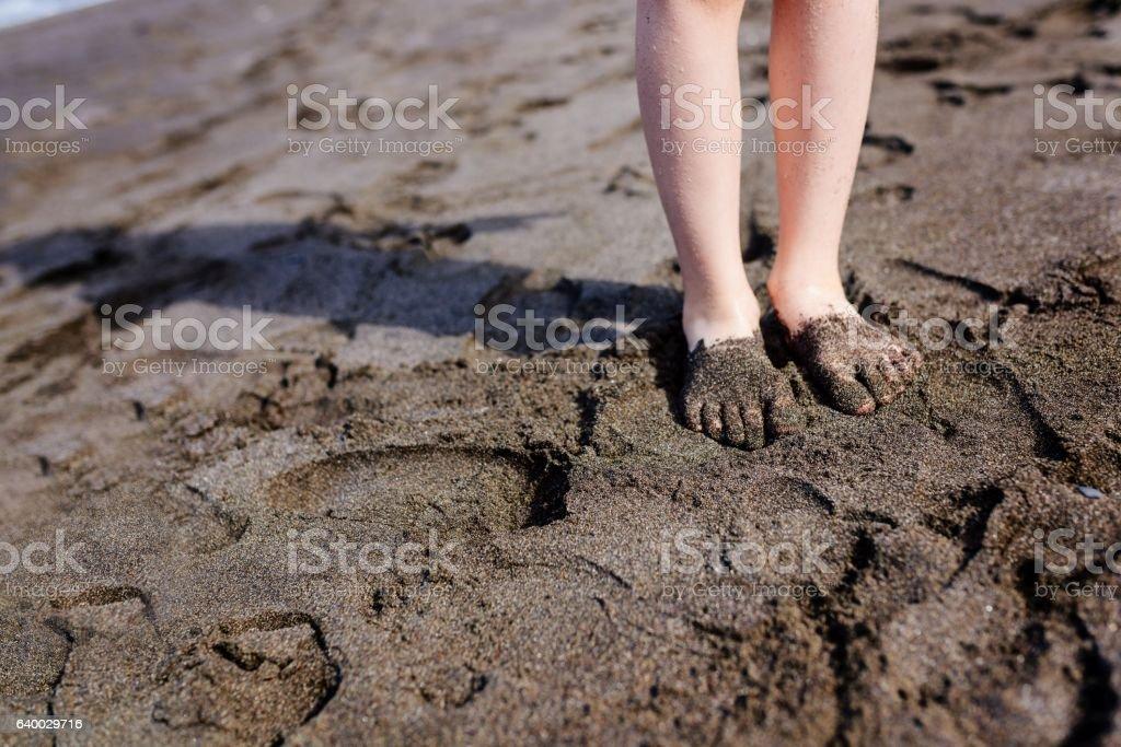 Child feet in dark volcanic sand on Tenerife beach stock photo