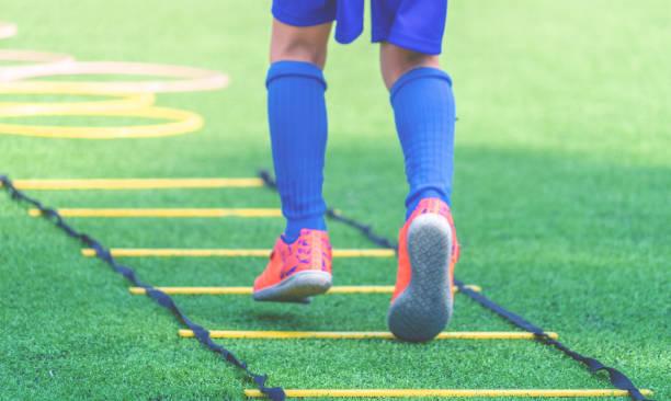 Pies infantiles con botas de fútbol entrenando en la escalera de velocidad de agilidad en entrenamiento de fútbol. - foto de stock