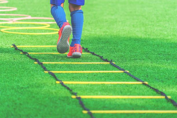 Pies de niño con botas de fútbol entrenando en la escala de velocidad de agilidad en el entrenamiento de fútbol. - foto de stock