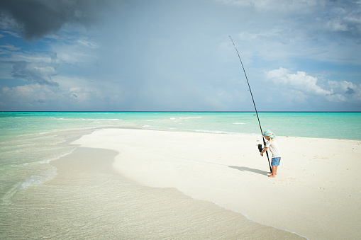 A child fishes on a sandbank in the tropics by himself with a long  fishing rod