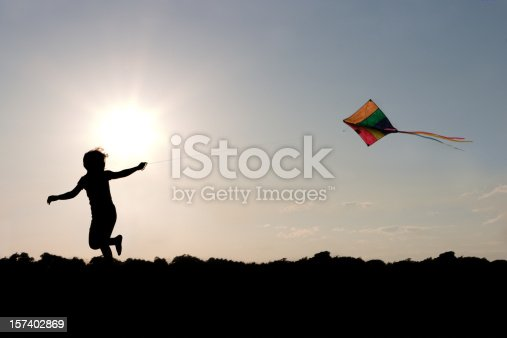 A silhouette of a child running and flying a kite.
