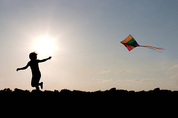 Child flying a multicolored kite outside stock photo