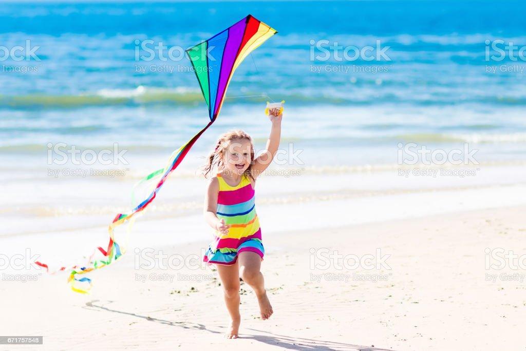 Child flying kite on tropical beach - foto stock