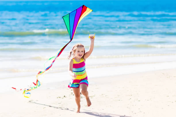 Child flying kite on tropical beach - foto stock