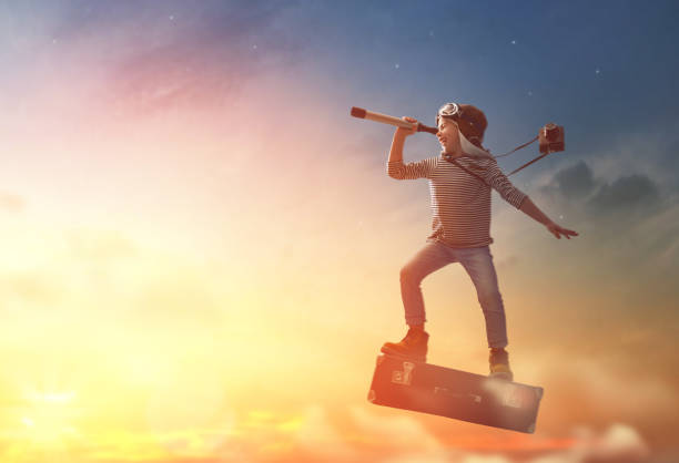 child flying on a suitcase - dreamlike stock photos and pictures
