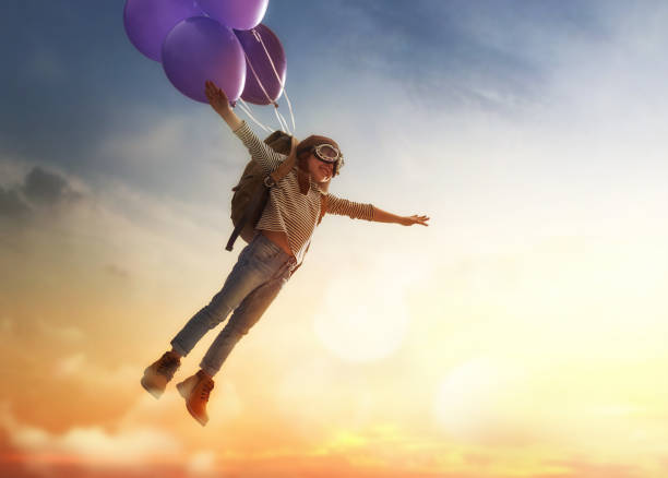Child flying on balloons stock photo