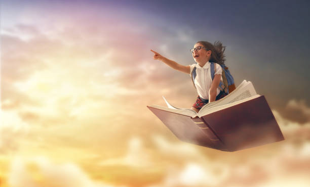 child flying on the book Back to school! Happy cute industrious child flying on the book on background of sunset sky. Concept of education and reading. The development of the imagination. flying stock pictures, royalty-free photos & images