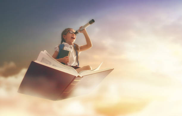 child flying on the book - imagination stock photos and pictures