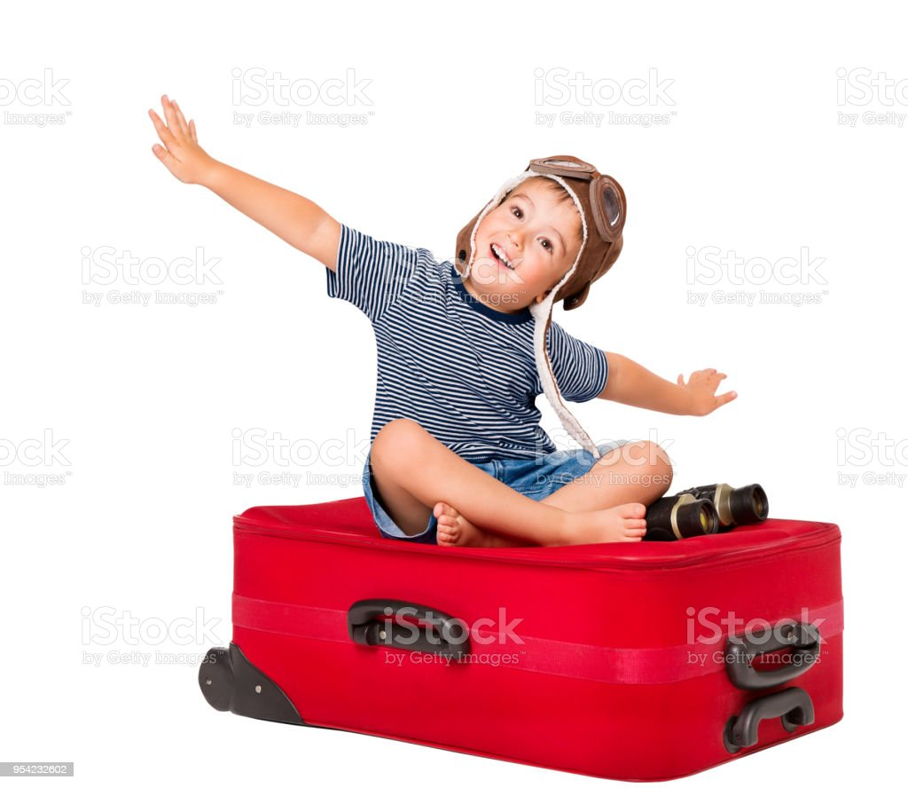Child Flying on Travel Suitcase, Kid Pilot in Aviator Hat Sitting on Red Luggage, Baby Boy White Isolated stock photo