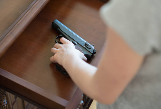 Child found pistol in drawer at home. stock photo