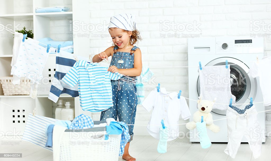 child fun  girl  to wash clothes and laughs in laund stock photo