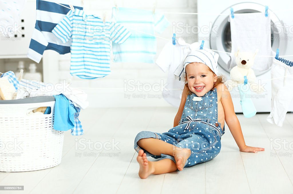 child fun happy little girl  to wash clothes and laughs stock photo