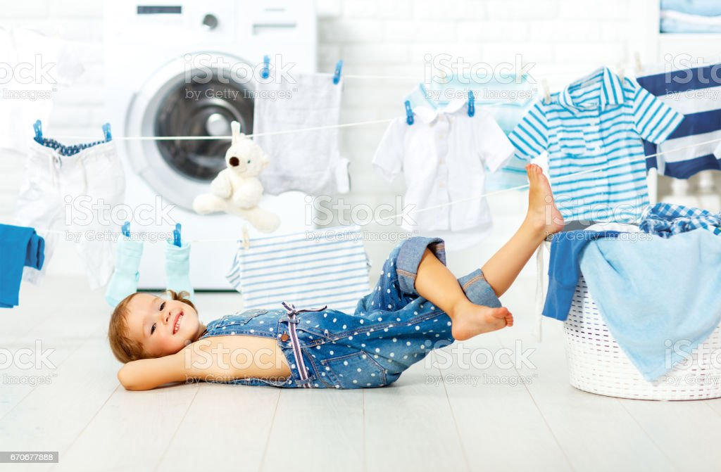 child fun happy little girl to wash clothes in laundry room stock photo