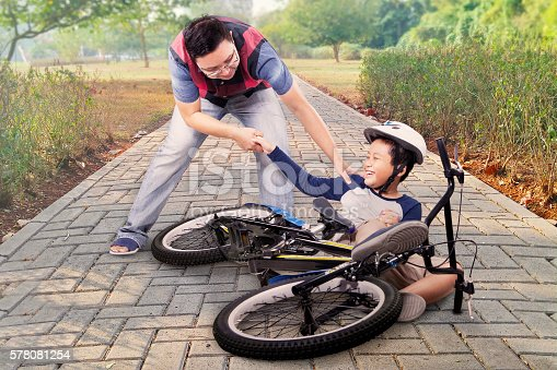 istock Child gets crash and helped by dad 578081254