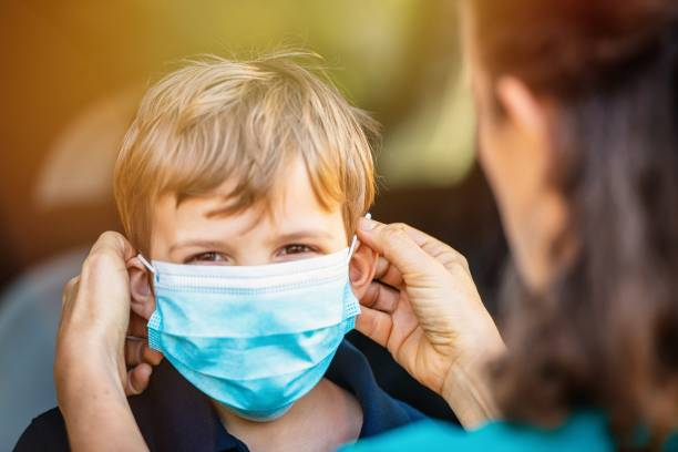 Child getting ready to go to school in pandemic times Caucasian Child getting ready to go to school in pandemic times, his mom is helping him to wear mask before he goes to school flatten the curve stock pictures, royalty-free photos & images